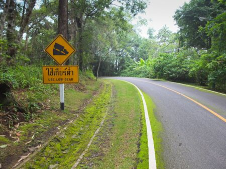 Use low gear and steep grade warning signs beside a downhill sharp curve in Chiang Mai,Thailand. Horizontal shot Stock Photo