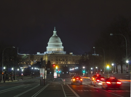 Capitol seen from Pennsylvania Avenue  Night time with traffic rushing by   photo