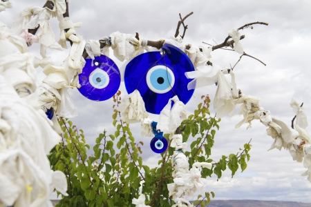 Evil eye charms hang from a bare tree in Cappadocia, Turkey   photo