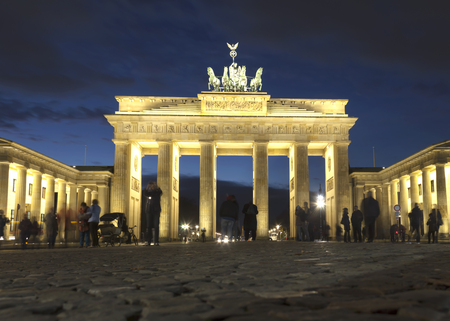 tourismus: The floodlit Brandenburg Gate in Berlin with a few fleeting shadows of Berlins anonymous - Symbol of Germany. Stock Photo