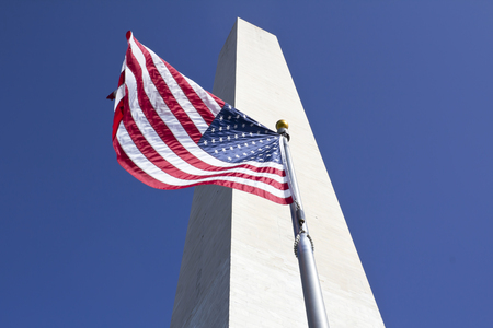 flapping: Washington Monument in Washington DC with american flag flapping on a flagpole