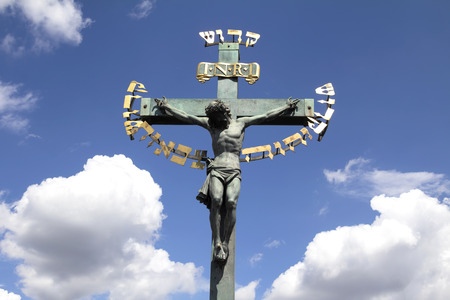PRAGUE, CZECH REPUBLIC - JULY 30, 2016: 17th Century Crucifixion statue with Hebrew lettering in Charles Bridge in Prague, Czech Republic Stock Photo