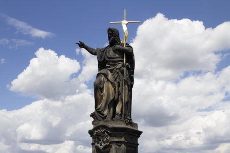 Statue of Saint John the Baptist at the Charles Bridge, holding the cross in golden armor feelings and emotions using right hand pointing the finger to the Prague castle, Prague