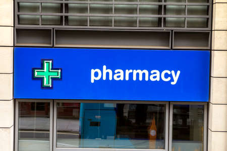 London, England : Pharmacy store entrance and sign pharmacy in downtown city during daytime 新聞圖片