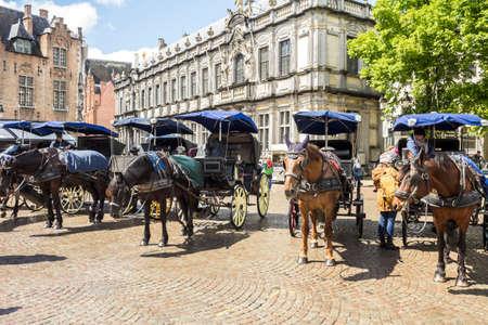 Bruges, Belgium - May, 2019: Horse-drawn carriages on Markt (Market) Square in Brugge (Bruges)