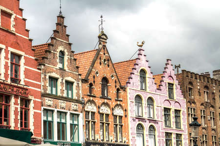 Famous old colorful buildings at Market square in Bruges, Belgium. Popular Flemish city with almost intact medieval architecture.