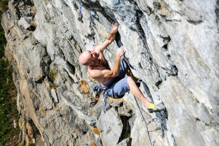 Climber while facing a wall of rock in the Alps, Northern Italy photo