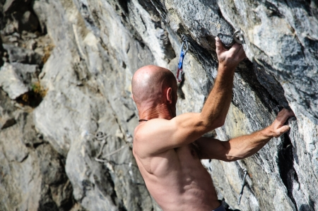 Climber while facing a wall of rock in the Alps, Northern Italy Stock Photo