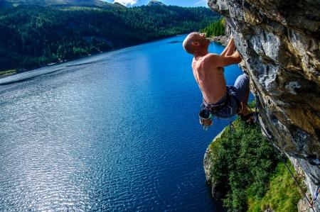 Climber climbing a rock wall above Lake Devero, Northern Italy Stock Photo - 16222035