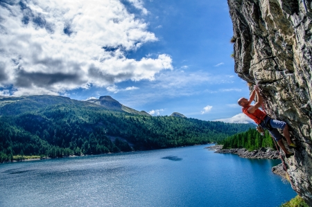 tenacity: Climber climbing a rock wall above Lake Devero, Northern Italy