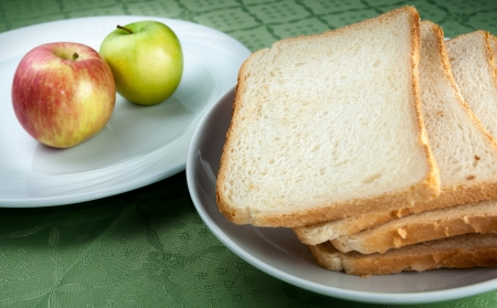 Slices of toast bread and apples on two white plates Stock Photo