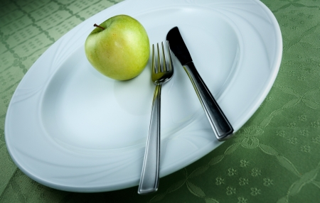 Green apple on a white plate with cutlery