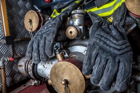 coche de bomberos: Guantes ign�fugos de un bombero que cuelga en el injerto de mangueras contraincendios de un viejo cami�n de bomberos Foto de archivo