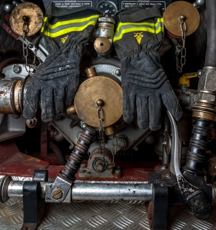 Fireproof gloves of a firefighter hanging on the graft of fire hoses of an old fire truck  photo