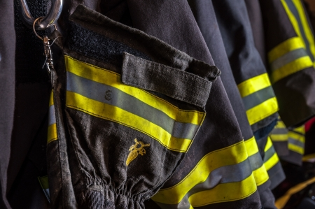 Fireproof suits of a team of firefighters ready to be worn for an emergency in a fire house photo