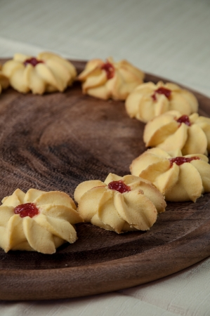 Tea biscuits arranged on a wooden round tray with flour, eggs, vanilla and jam.