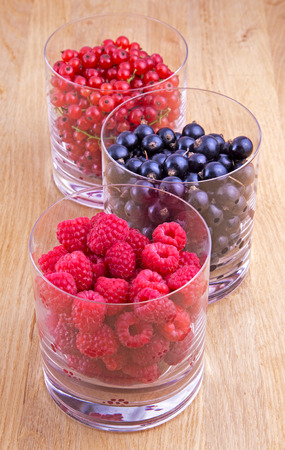 Black, red currants and raspberries in glasses on wooden background photo