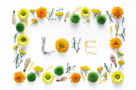 Creative frame and word LOVE made of flowers on white background.