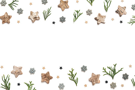 Winter pattern with cypress twigs and christmas ornaments (wooden stars and snowflakes) on white background. View from above.