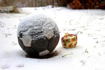 Beautifull Christmas apple and a soccer ball in the snow.