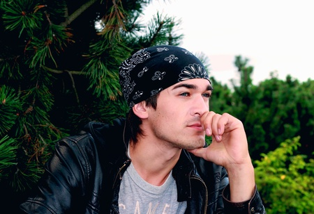 A handsome man in a bandana and a leather jacket in black with a hand from a person in thought