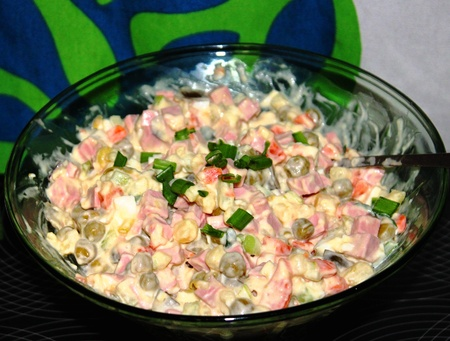 salad in the Russian tradition in a bowl, sprinkled with green onions