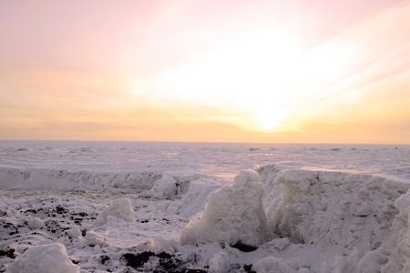 Beautiful winter sunset. Kind on a freezing sea and precipice