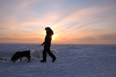 Men with rottweiler. Winter view to the beach. Beautiful sunset photo