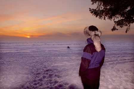 A portrait of man is in a fur cap in winter sunset photo