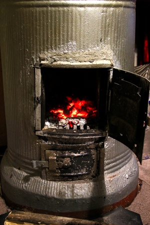 an old stove with burning coals and wood