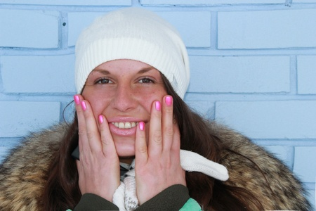 Woman on bright background is smiling in winter cloth  Stock Photo