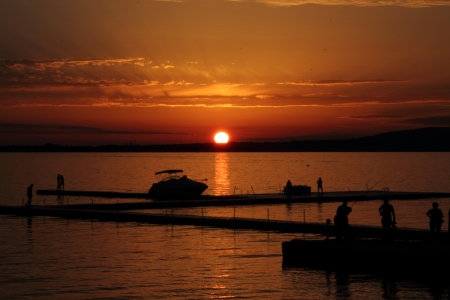 Golden sunset in Gelendzhik. Cather, Shadows of people, fishermen. Russia