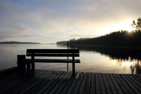 Landscape with lake pier in Finland. Bench at sunrise Stock Photo