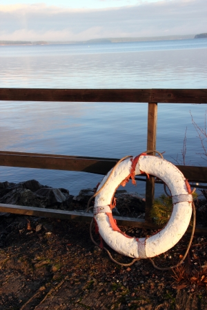 Lifebuoy white and red color on a lake in Finland photo