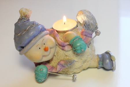 Cheerful snowman skier. Candlestick with burning candle Stock Photo