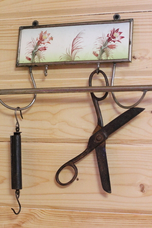 Vintage composition on the background of a wooden wall. Hanger, scissors, scales Stock Photo