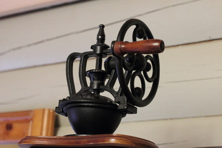 Vintage coffee grinder made of wood and black wrought metal