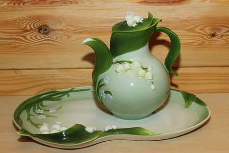 jug with lilies of the valley on a platter. Stock Photo