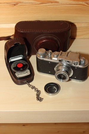 Vintage camera on a wooden background. light meter