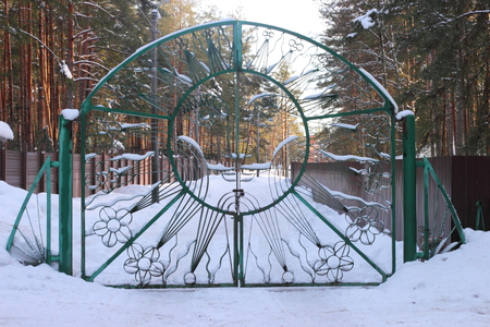 Wrought-iron gate with the image of the sun with a smile green