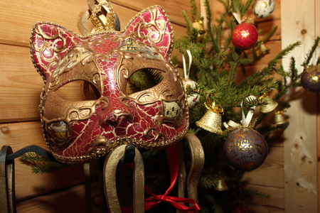 Christmas composition bouquet of tree with toys and the Venice mask in a wooden house