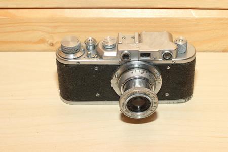 Vintage camera on a wooden background. Black, metal