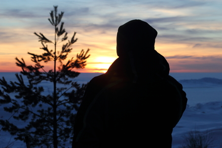 man in  the sunset on the Gulf of Finland with trees