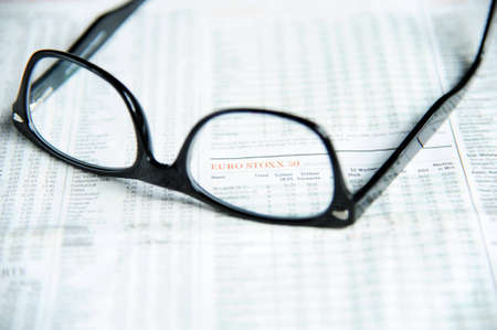 financial newspaper: Glasses on a financial newspaper