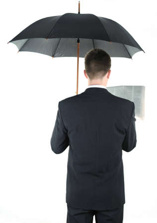 Businessman with an umbrella reading a newspaper photo