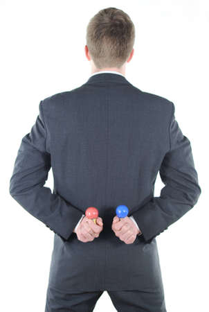 Businessman with red and blue light bulb behind his back photo