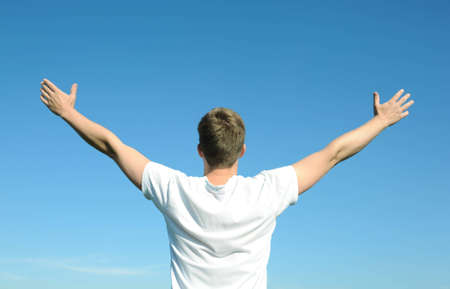 Young man in white t-shirt with arms open, blue sky photo