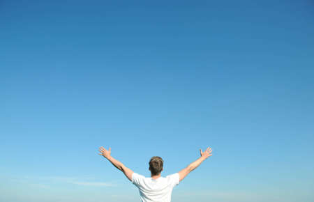 wondering: Young man in white t-shirt, arms open and blue sky