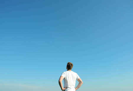 blue sky thinking: Young man in white t-shirt looking at the blue sky