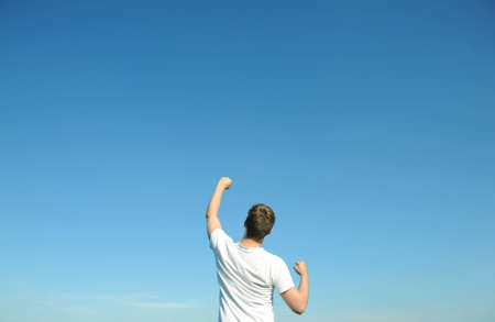 indicating: Young man in white t-shirt, blue sky. Above space for text or graphics.